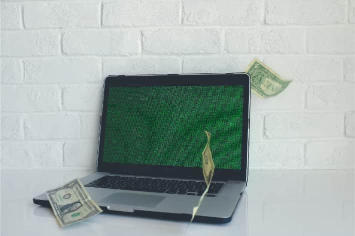 Equipo portátil hackeado con billetes de dólares cayendo